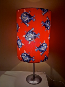 This-handmade-lampshade-is-fitted-in-a-retro-kids-fabric-that-shows-joyous-blue-monsters-cavorting-against-a-crimson-background-was-created-by-The-Lost-And-Found-Office-Australia